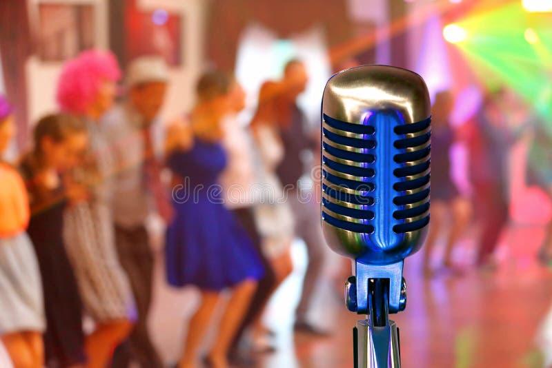 Retro- Mikrofon am Konzert mit tanzenden Leuten der Menge und leerer Raum für Text lizenzfreie stockbilder