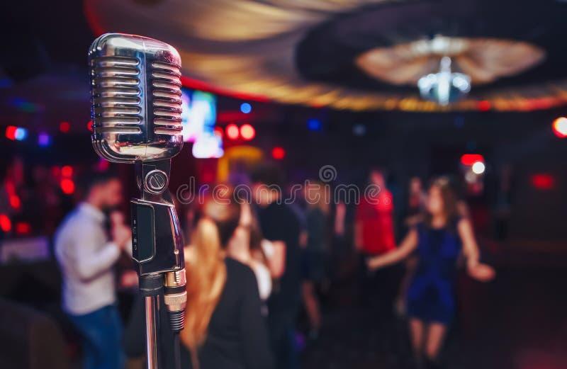 Retro mikrofon przeciw plamy kolorowemu lekkiemu tłu zdjęcia royalty free