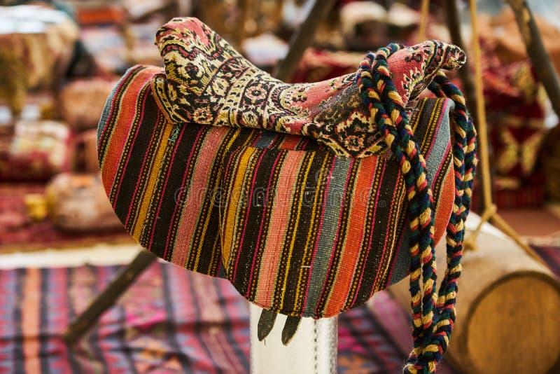 Retro mjuk åsnasadel, närbild Gammal färgrik hästsadel arkivfoton