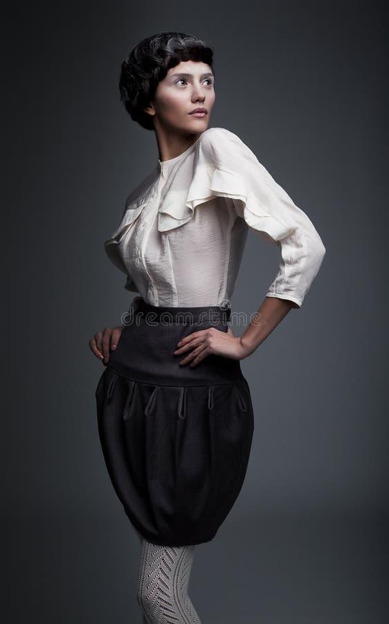 Retro model het branden van de manier brunette die omhoog eruit ziet royalty-vrije stock fotografie