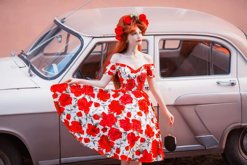 Retro model with red lips in summer flower dress on car background. Redhead girl with black bag and near retro car. Valentine card royalty free stock photography