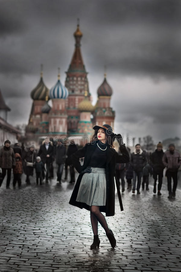Retro in modern. Retro style fashion woman on background of grey crowd of people in Moscow center