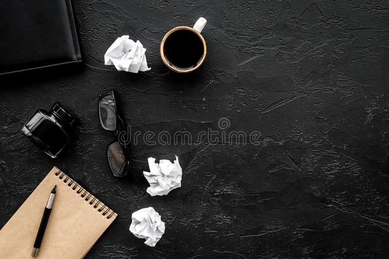 Retro and modern writer desktop with coffee, notebook and ink on black table background top view mock up royalty free stock photography
