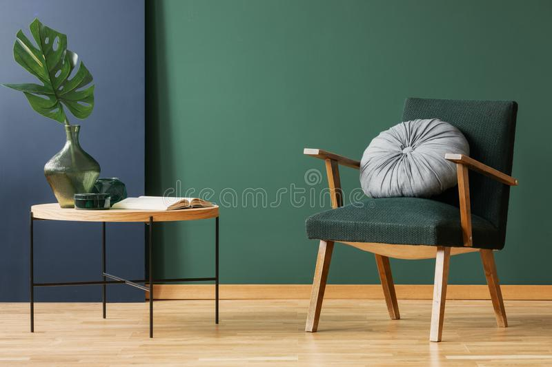 Retro moss green armchair with round, silver pillow next to wooden coffee table with leaf in glass vase, copy space on empty wall. Concept photo stock photo