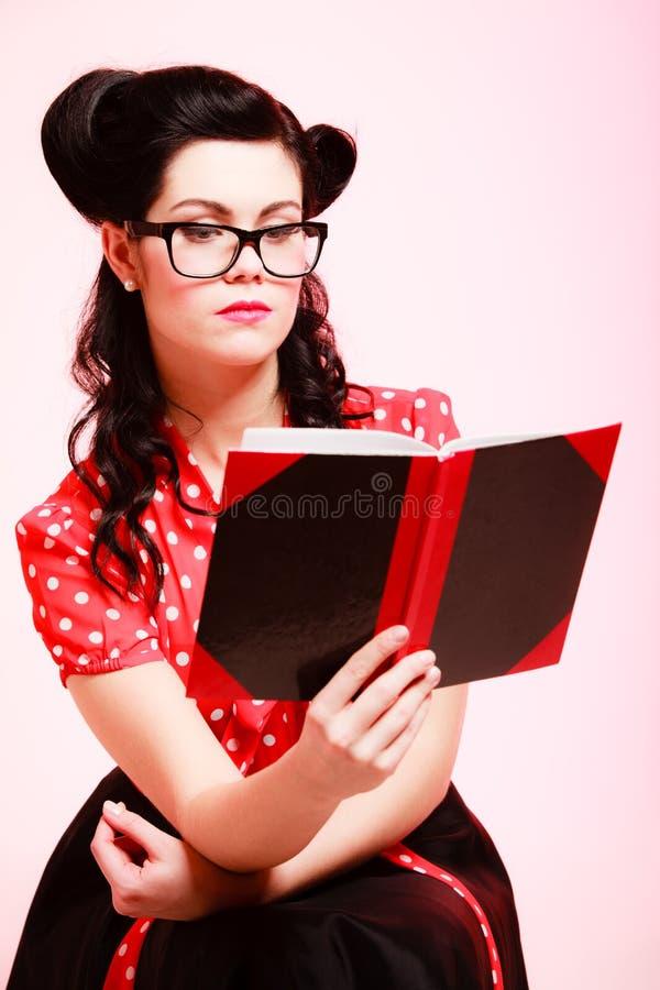 retro Muchacha modela en libro de lectura de las lentes imagen de archivo