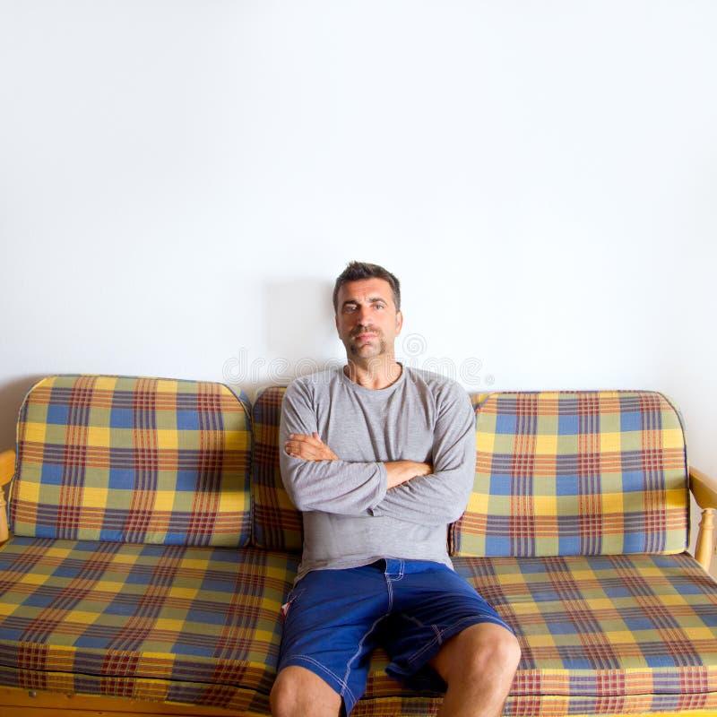 Retro mustaschman som sitter i tappningsofa royaltyfri fotografi