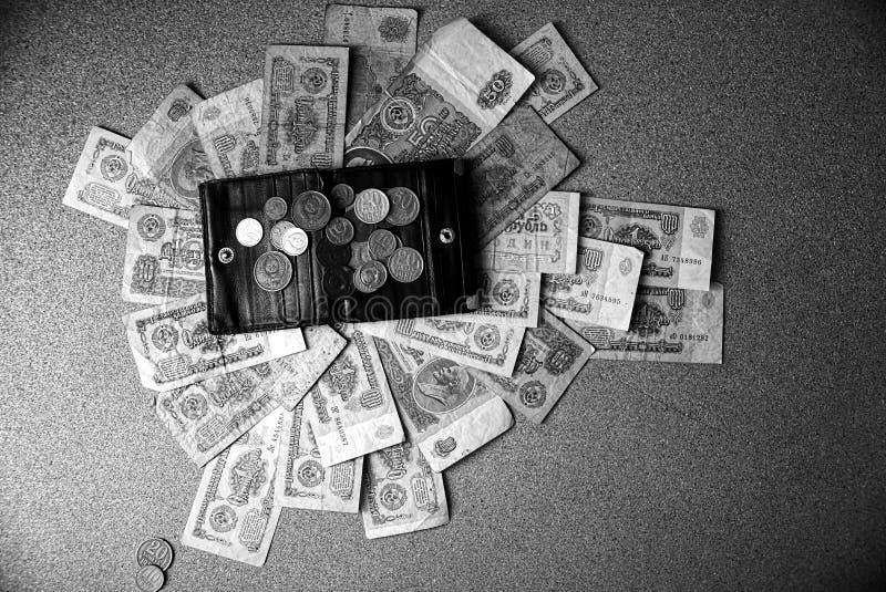 Retro mynt spridda på en svart handväska och räkningar på tabellen arkivbild