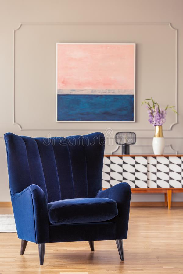 Retro, navy blue armchair in an elegant living room interior with an abstract painting on a wall. With molding stock photography