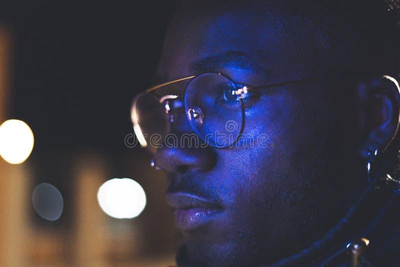 Retro- Neonporträt eines Afroamerikaners Schwarzer Mann mit modernen Gläsern stockfoto