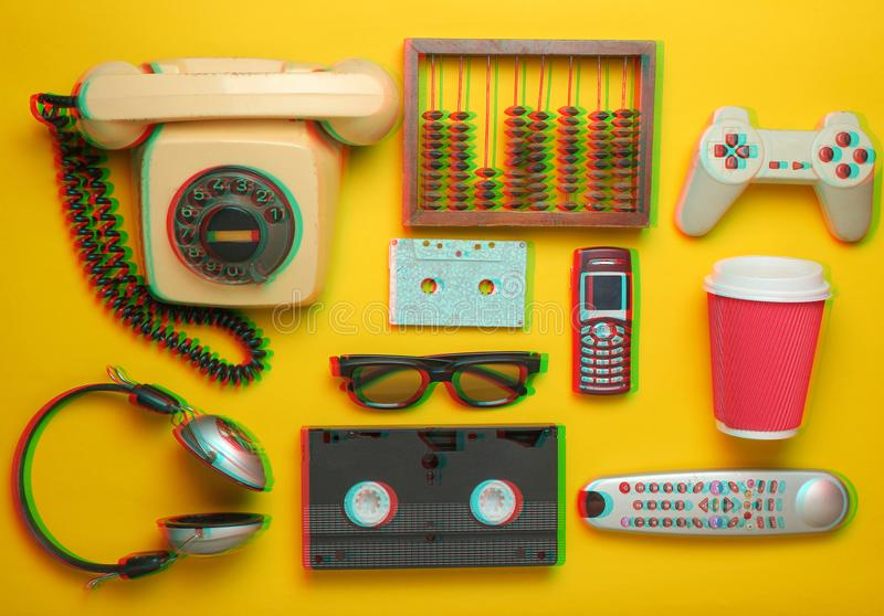 Retro objects on a yellow background. Rotary telephone, audio cassette, video cassette, gamepad, 3d glasses stock photo