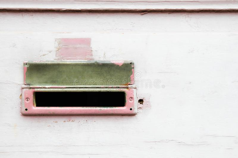 Retro old pink and white mailbox vintage postal box mounted on a cracked, grungy wall. Retro old pink and white mailbox vintage postal box mounted on a cracked royalty free stock images