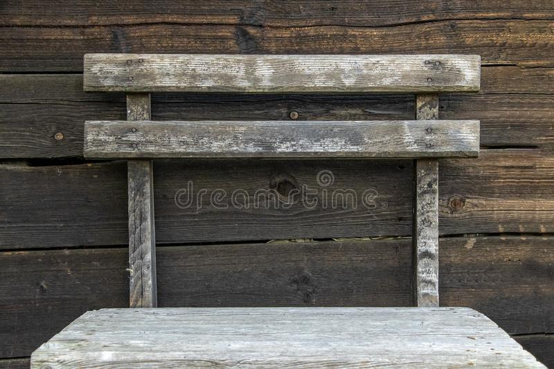 Retro old wooden chair. Old burned boards with nails in brown and black colour as a background. a wooden chair stands before that. This is nature background in royalty free stock photo