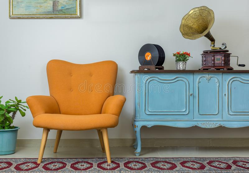 Retro orange armchair and vintage wooden light blue sideboard royalty free stock photos
