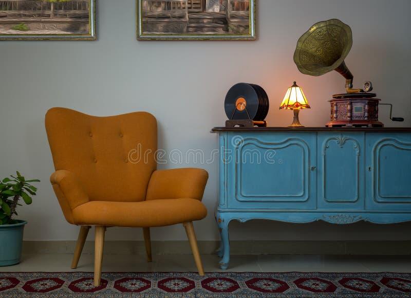 Retro- orange Lehnsessel, hölzerne hellblaue Anrichte der Weinlese, altes Plattenspielergrammophon, Vinylaufzeichnungen und belic stockbild