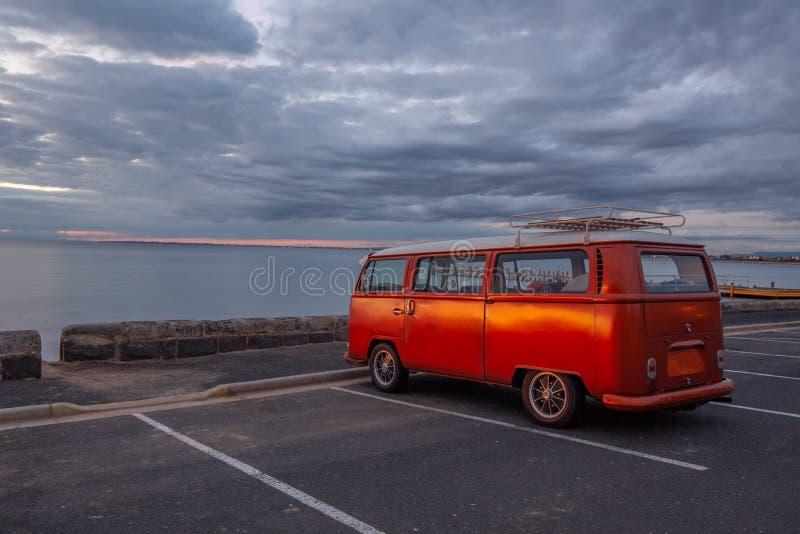 Retro oranje bestelwagen op het oceaanstrand royalty-vrije stock fotografie