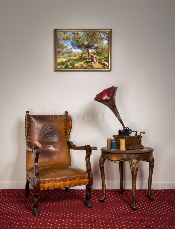Retro ornate armchair, old phonograph, cylinders on round coffee table stock photos