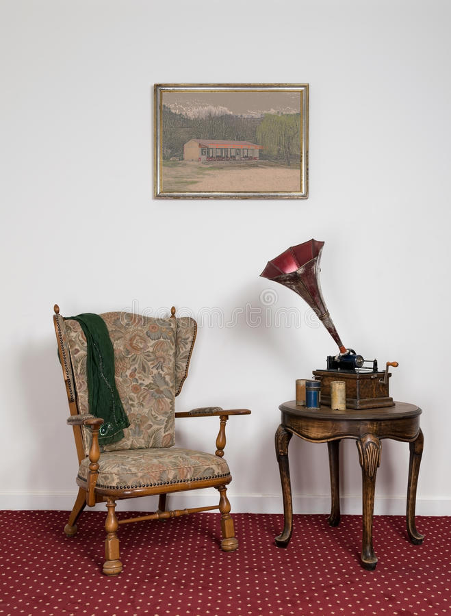 Retro ornate armchair, old phonograph, cylinders on round coffee table royalty free stock photos