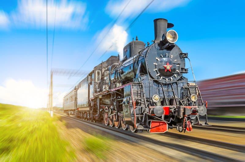 Retro oude stoom voortbewegingsstormlopen bij snelheid met een passagierstrein royalty-vrije stock afbeeldingen