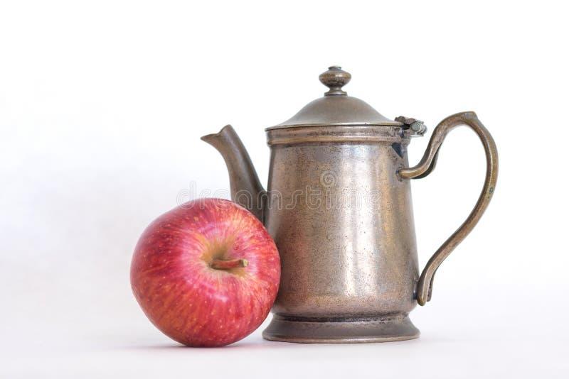 Retro ouderwetse theepot van de tin antieke, zilveren kleur met een inlands rood - heerlijke appel naast het op een witte achterg stock fotografie
