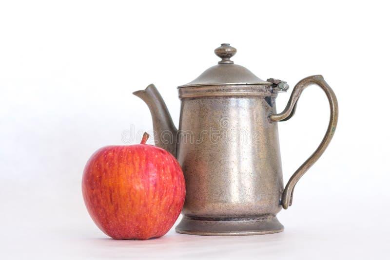 Retro ouderwetse theepot van de tin antieke, zilveren kleur met een inlands rood - heerlijke appel naast het op een witte achterg royalty-vrije stock afbeelding