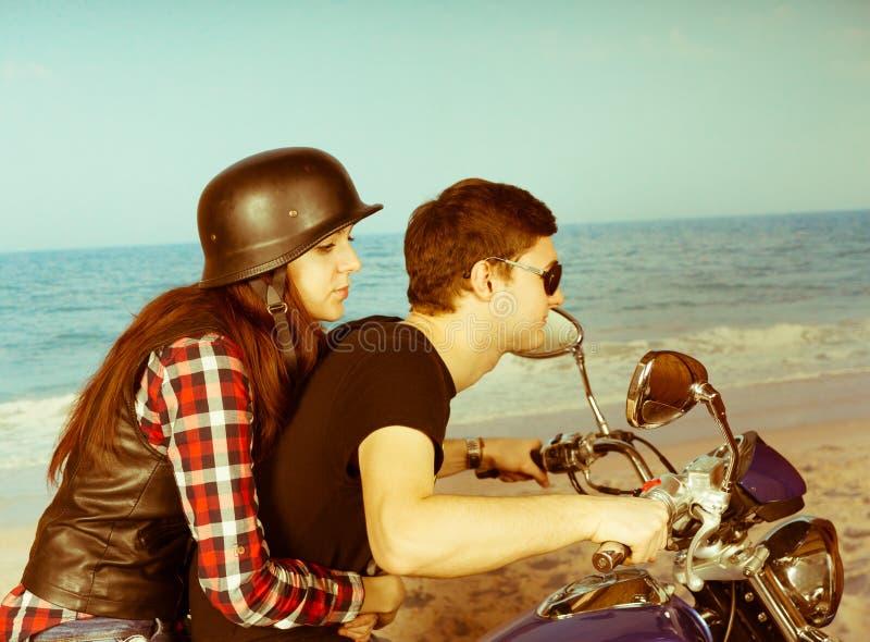 Retro par som rider en moped på stranden royaltyfri foto
