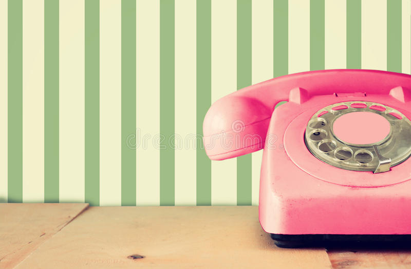 Retro pastel pink telephone on wooden table and abstract retro geometric pastel pattern Background. retro filtered image stock images