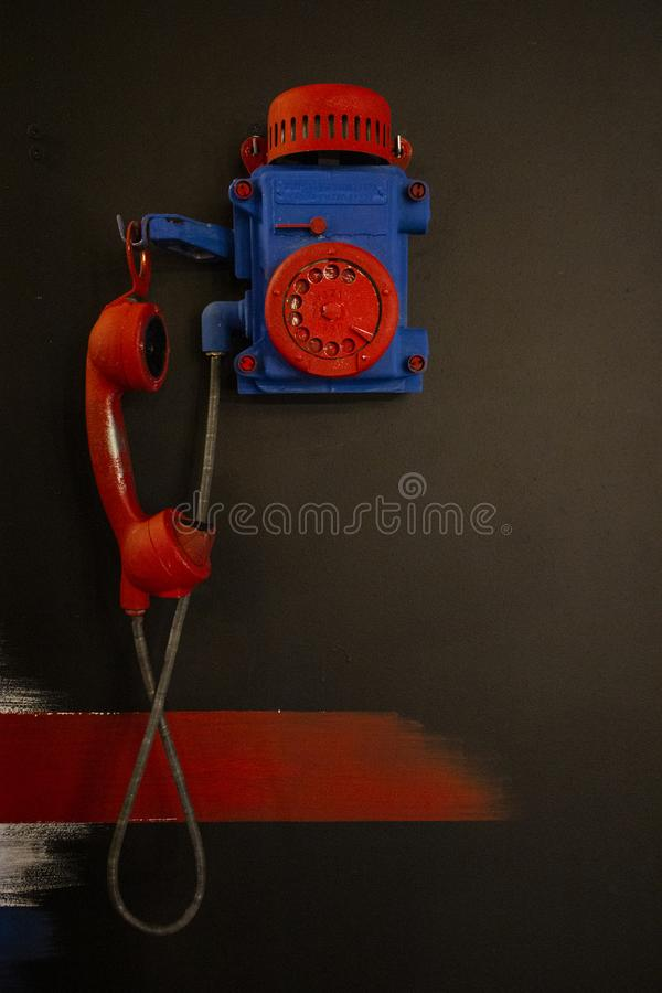 Retro payphone in red and blue color. On the black background royalty free stock photography