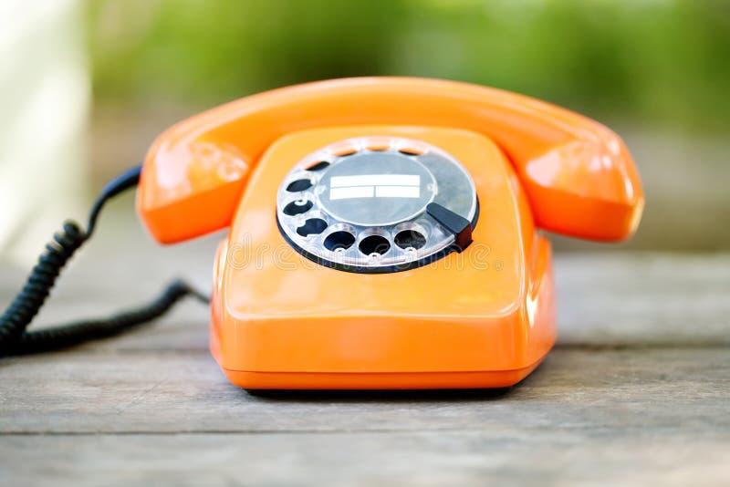 Retro phone orange color, handset receiver on wooden textured background. Shallow depth field photography. Retro phone orange color, handset receiver on wooden stock photography