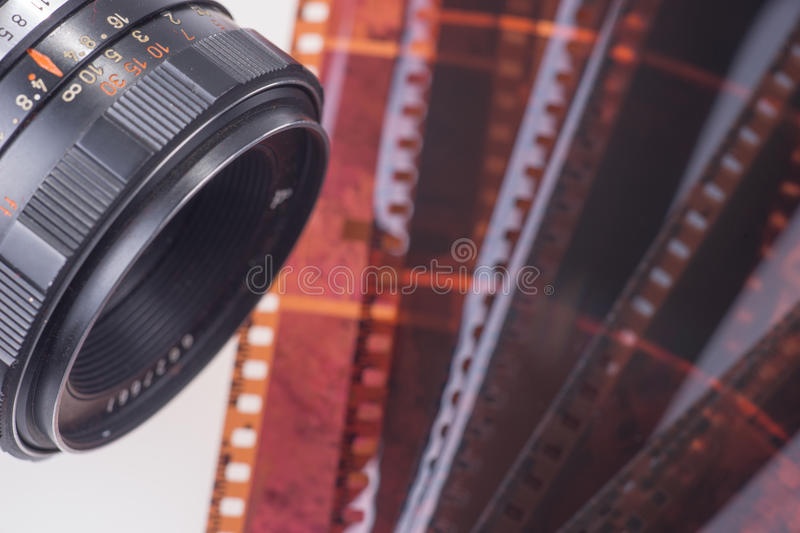 Retro photo camera with film strip. Isolated on white royalty free stock images