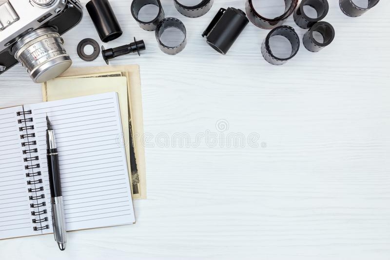 retro photo camera, open notebook and negative films rolls on white wooden board royalty free stock photos