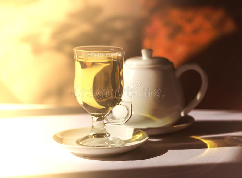 Retro photo of a glass of tea and a kettle royalty free stock image