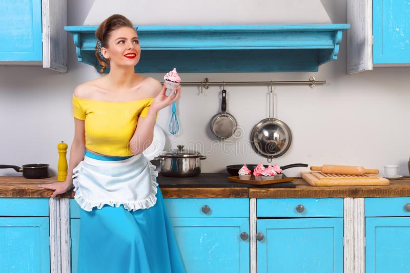 Retro pin up colorful woman housewife. Retro pin up beauty girl woman female housewife wearing colorful top, skirt and white apron holding cooked sweet cupcake royalty free stock images