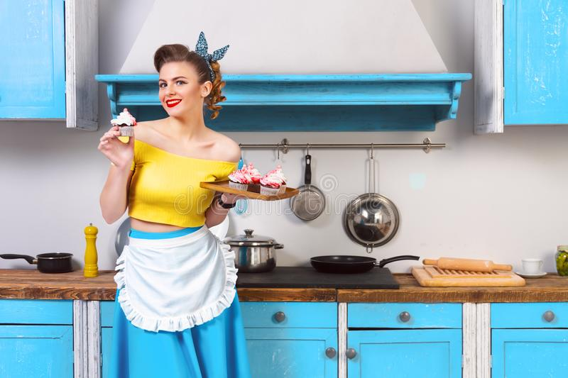 Retro pin up colorful woman housewife. Retro pin up cute colrful girl woman female housewife wearing colorful top, skirt and white apron holding tray with cooked stock photography