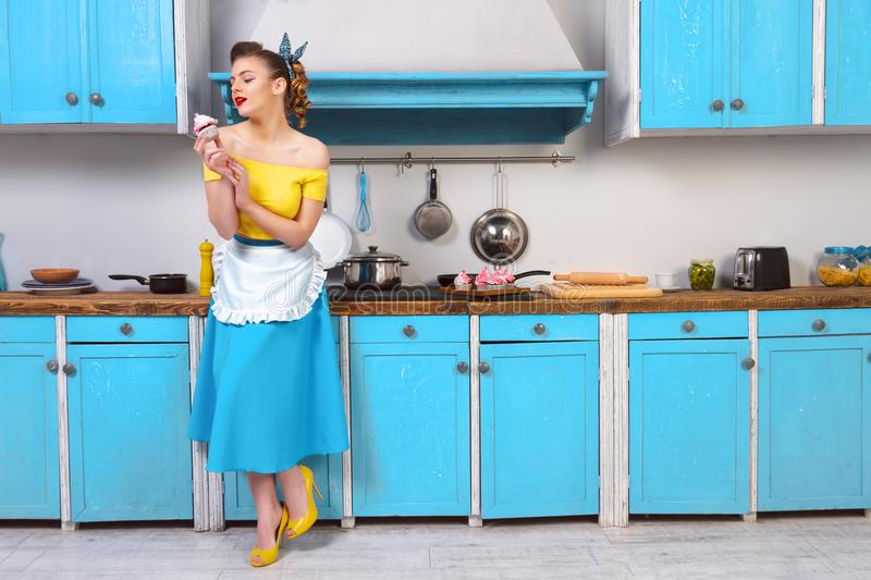Retro pin up colorful woman housewife. Retro pin up girl woman female housewife wearing colorful top, skirt and white apron and yellow high heels holding cooked stock photo