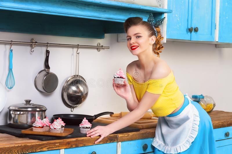 Retro pin up colorful woman housewife. Retro pin up beautifull girl woman female housewife wearing colorful top, skirt and white apron holding cooked sweet royalty free stock photography
