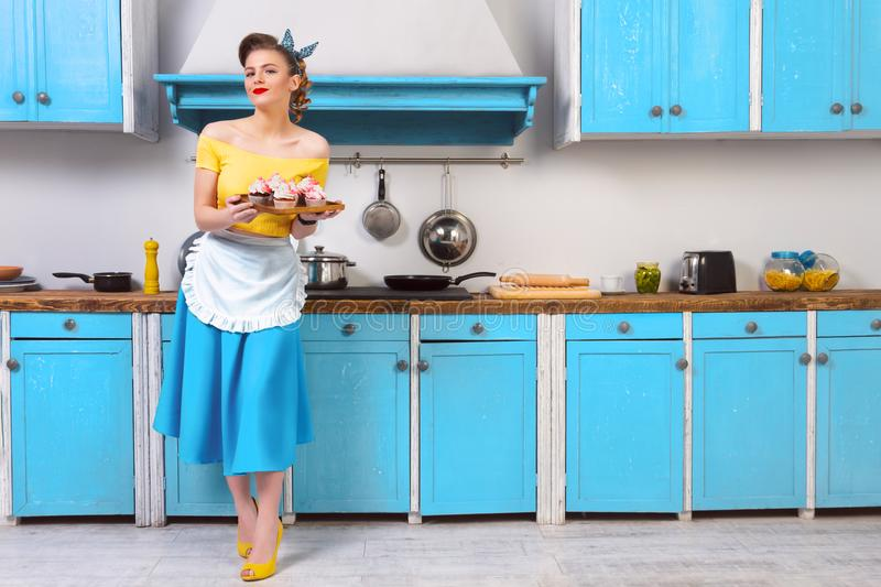 Retro pin up colorful woman housewife. Retro pin up girl woman female housewife wearing colorful top, skirt and white apron and yellow high heels holding tray stock image