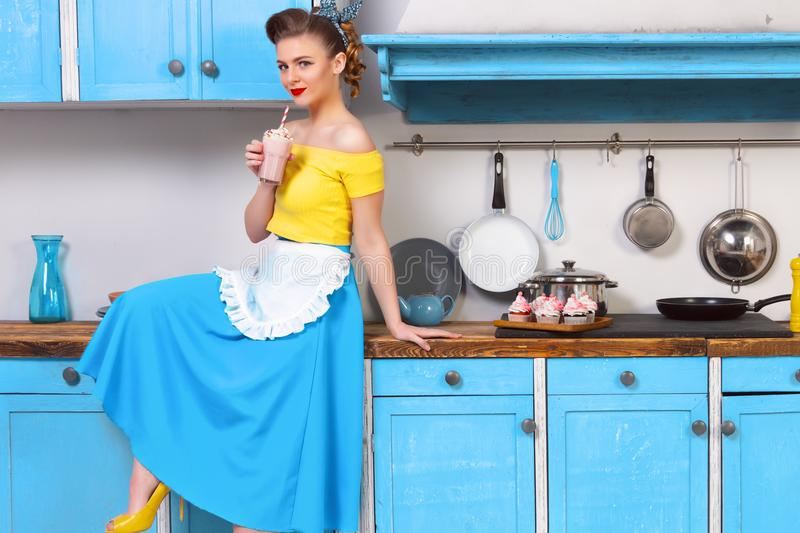 Retro pin up colorful woman housewife. Retro pin up girl woman female housewife wearing colorful top, skirt and white apron holding cooked sweet strawberry royalty free stock photos