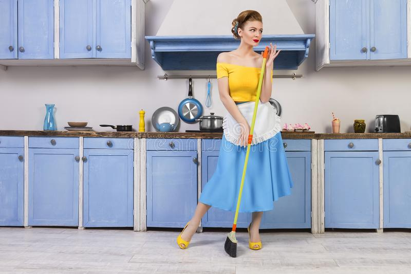 Retro pin up girl housewife in the kitchen. Colofrul retro / pin up girl woman female / housewife wearing colorful top, skirt and white apron holding mop and royalty free stock photo