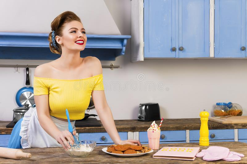 Retro pin up girl housewife in the kitchen. Colofrul retro / pin up girl woman female / housewife wearing colorful top, skirt and white apron cooking in the royalty free stock photos