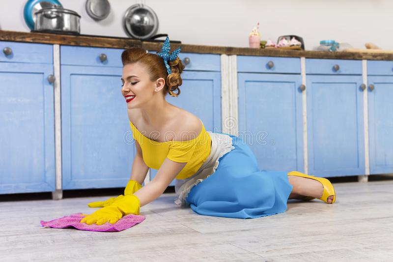 Retro pin up girl housewife in the kitchen. Colorful retro / pretty pin up girl woman female / housewife wearing colorful top, skirt and white apron cleaning stock photo