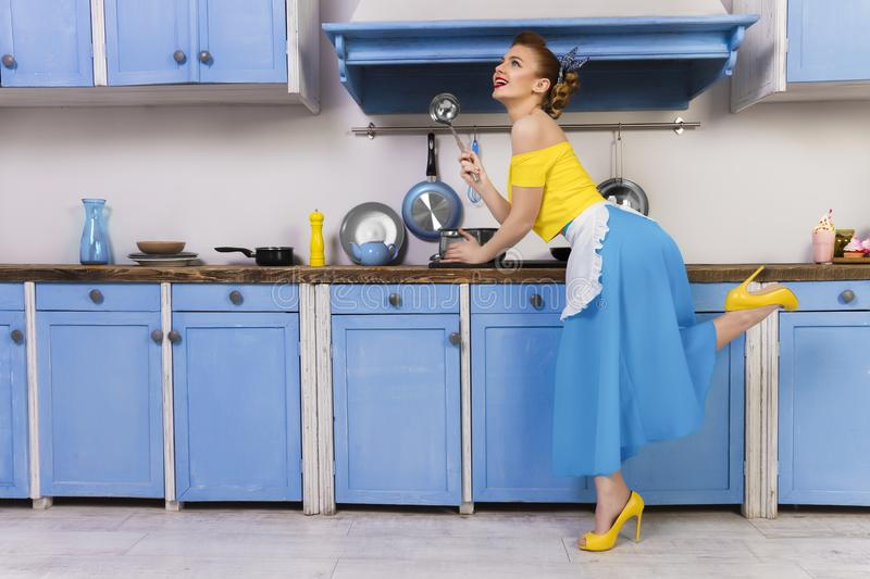 Retro pin up girl housewife in the kitchen. Colorful retro / pin up girl woman female / housewife wearing colorful top, skirt and white apron holding ladle and stock images