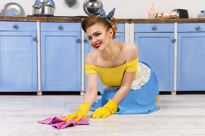 Retro pin up girl housewife in the kitchen. Colorful retro / pretty pin up girl woman female / housewife wearing colorful top, skirt and white apron cleaning royalty free stock image