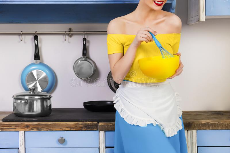 Retro pin up girl housewife in the kitchen. Colorful retro / pin up girl woman female / housewife wearing colorful top, skirt and white apron holding whipper and royalty free stock photos
