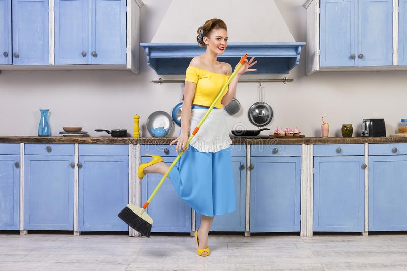 Retro pin up girl housewife in the kitchen. Retro / pin up girl female woman / housewife wearing colorful top, skirt and white apron holding mop and cleaning royalty free stock photos