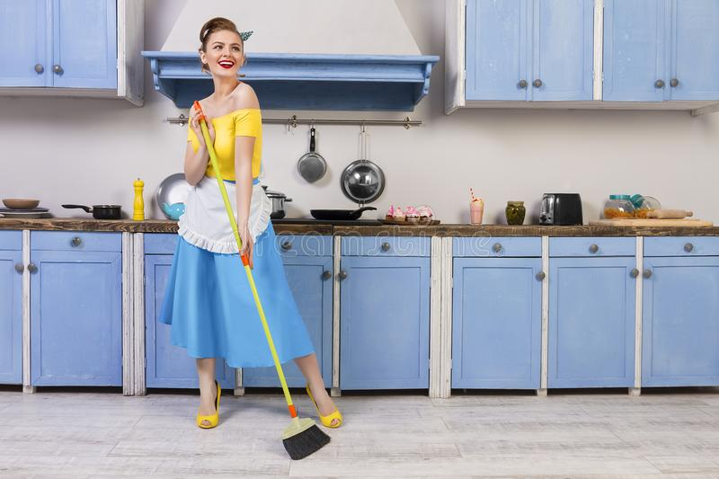 Retro pin up girl housewife in the kitchen royalty free stock photography