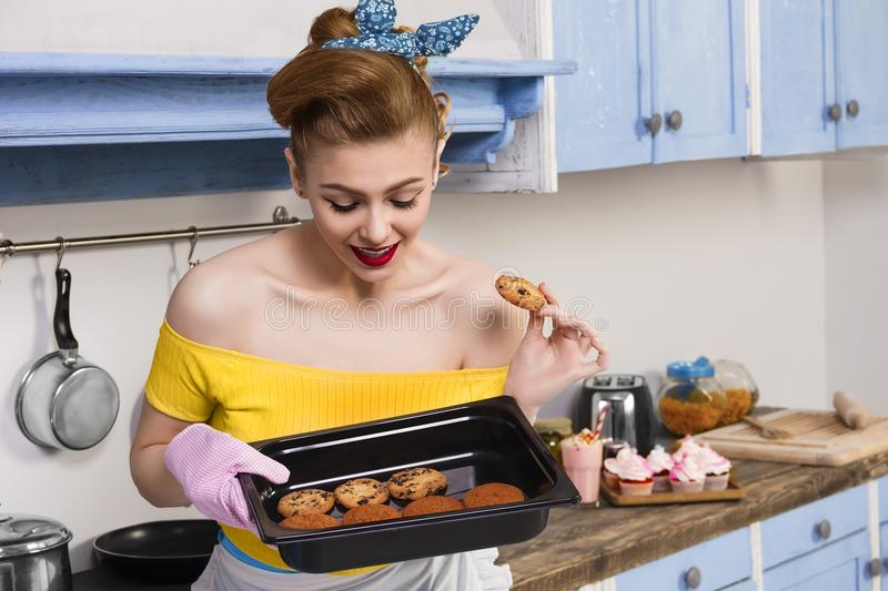 Retro pin up girl housewife in the kitchen. Retro pin up girl woman female / housewife wearing colorful top holding tray with home cooked cookies standing in the royalty free stock photography