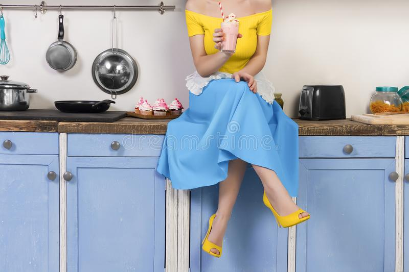 Retro pin up woman housewife sitting in the kitchen. Retro pin up girl woman female housewife wearing colorful top, skirt and white apron holding cooked sweet royalty free stock images