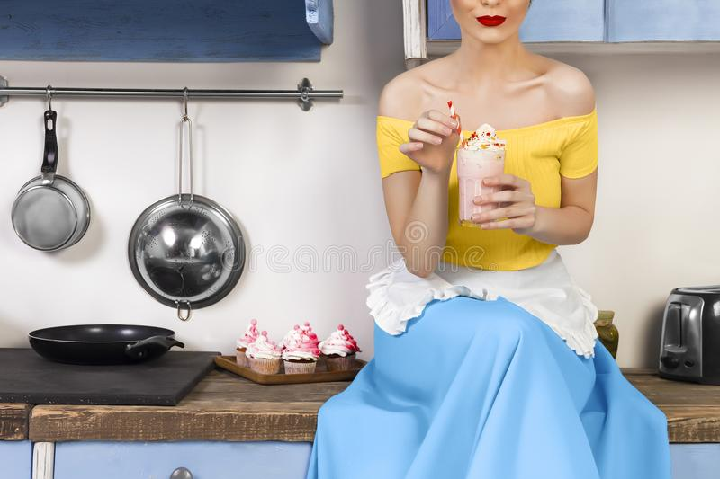 Retro pin up woman housewife sitting in the kitchen. Retro pin up girl woman female housewife wearing colorful top, skirt and white apron holding cooked sweet stock photography