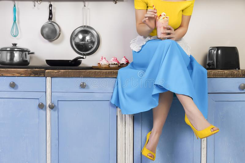 Retro pin up woman housewife sitting in the kitchen stock photo