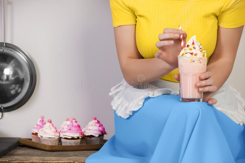 Retro pin up girl housewife in the kitchen. Retro pin up girl woman female housewife wearing colorful top, skirt and white apron holding cooked sweet strawberry stock photography